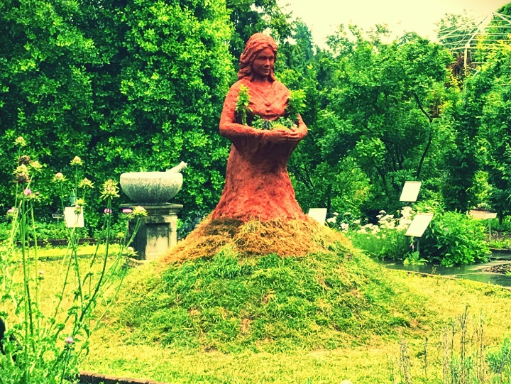 A red clay statue of a woman carrying live growing herbs appears to come out of an earthen mound of grass. There is a massive stone mortar and pestle behind her and botanical plants with healing properties ring the grass circle.